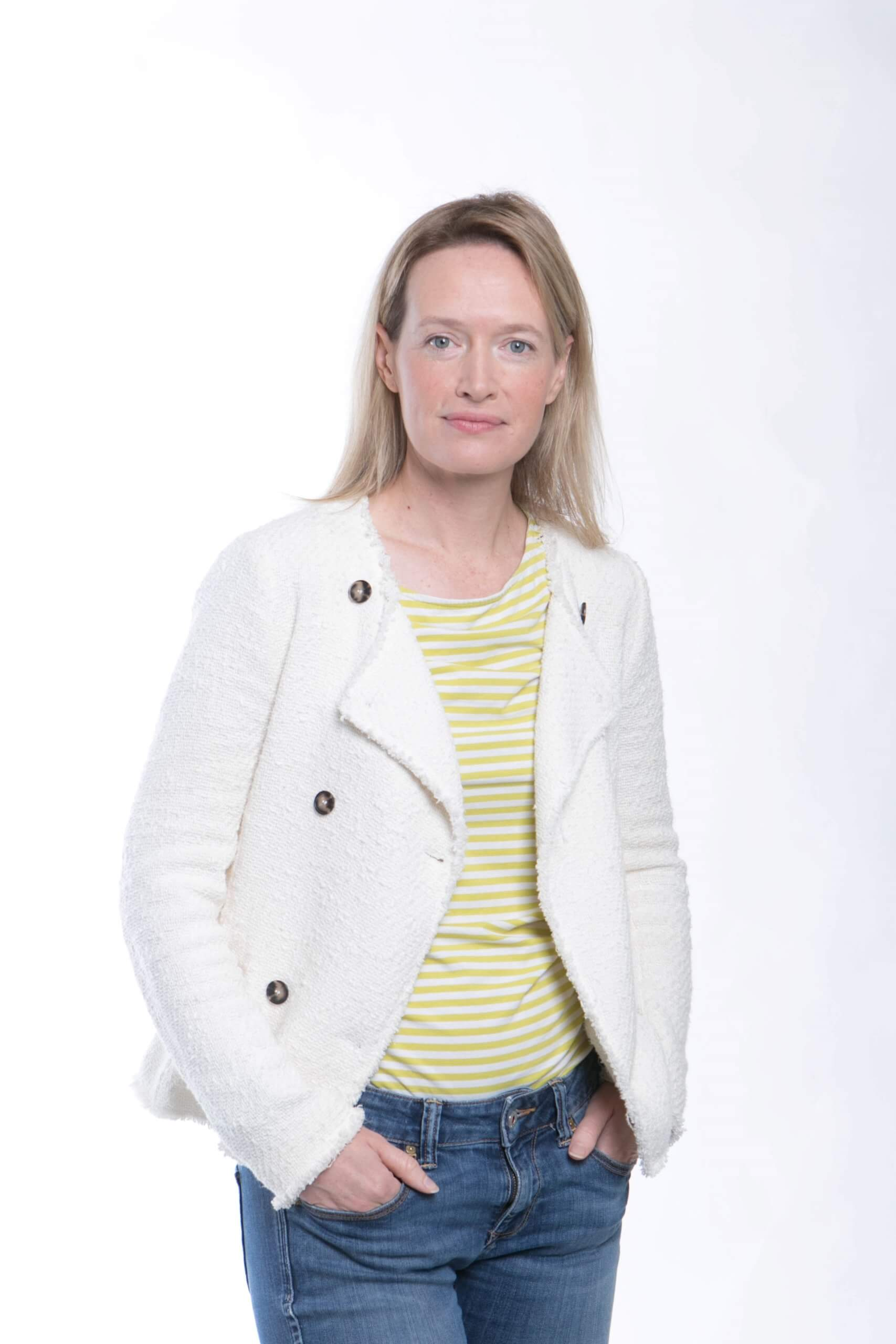 Vanessa Coffey looks at the camera, wearing a white jacket and yellow top, with hands in pockets of her jeans