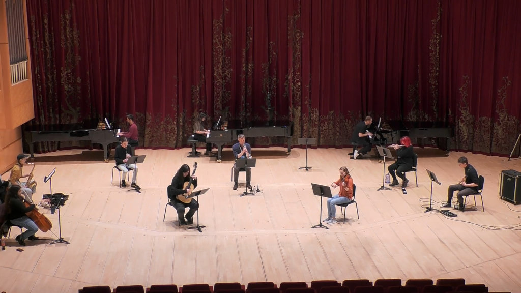 An ensemble of musicians spread across a stage.