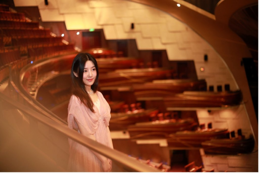 Composer Junqi Wan smiling in an auditorium.