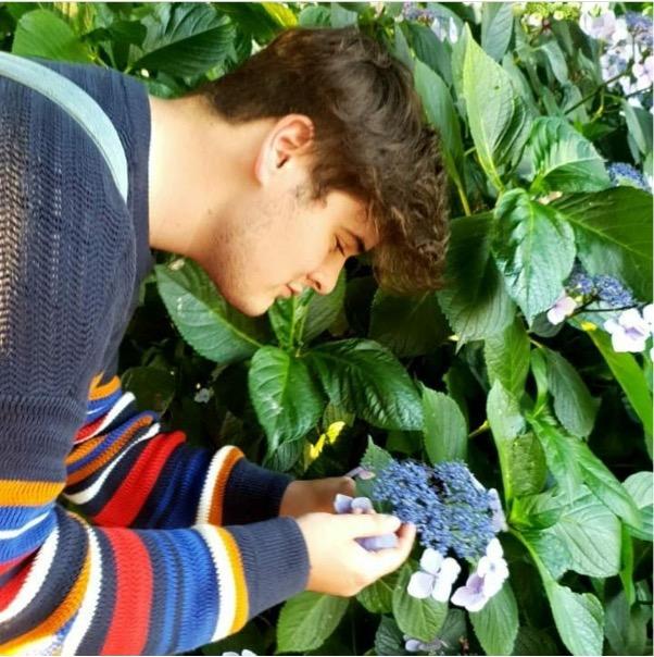 Composer Kerr McLean holding a blue flower.