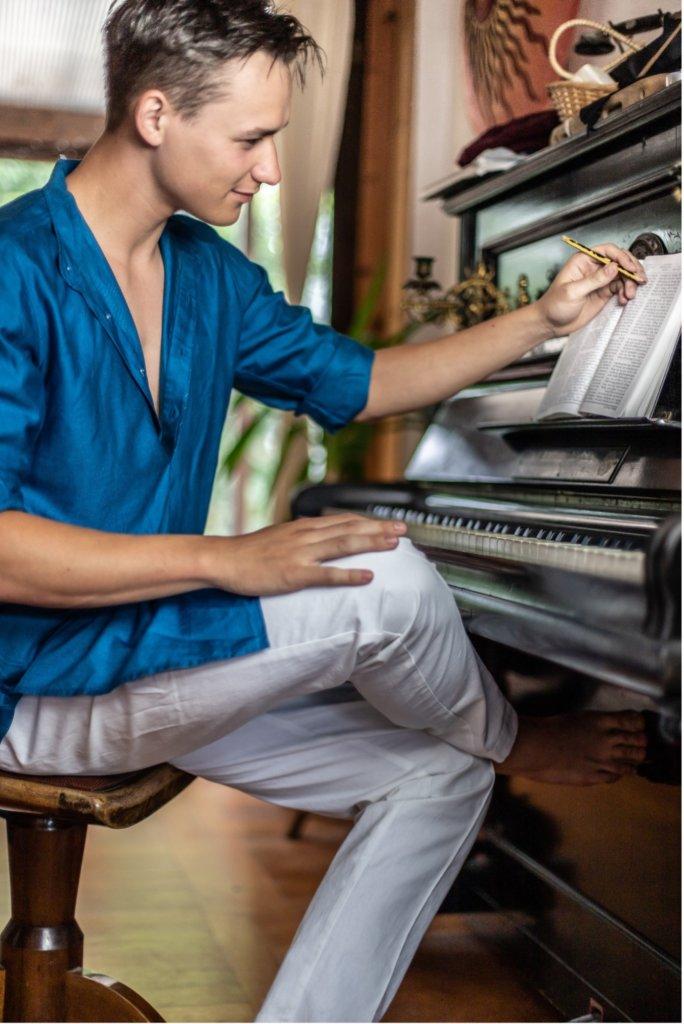 Composer Nils Benedikt Meier sitting at a piano.