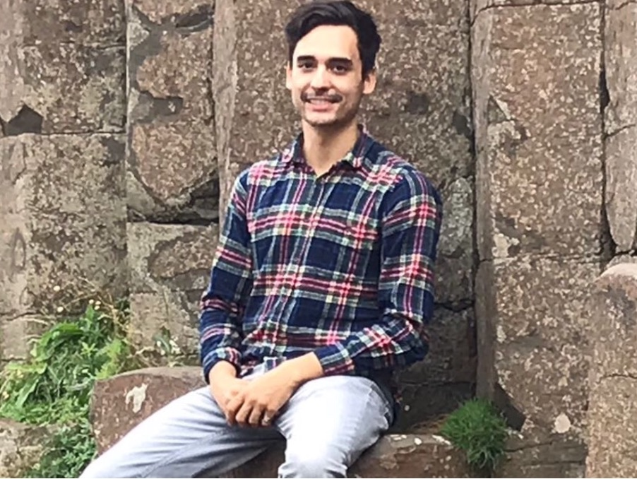 Composer Pablo Martinez smiling against a backdrop of rocks.