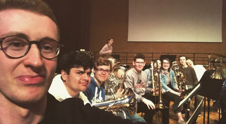 Gavin taking a picture of himself with an orchestra holding their instruments