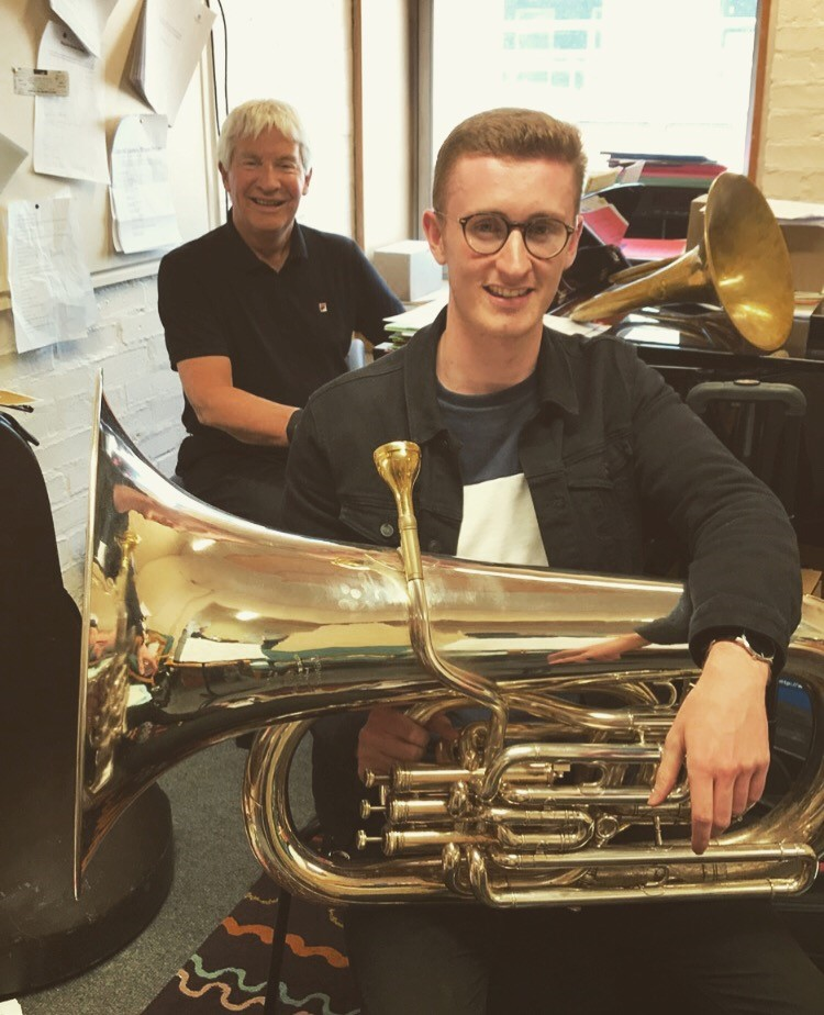 Gavin holding a tuba and sitting in front of lecturer Tony Swainson
