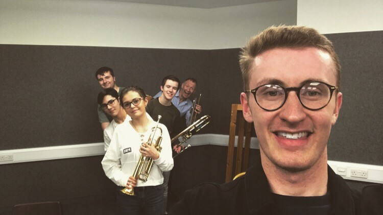 Picture of Gavin with the Brass Quintet Group holding their instruments