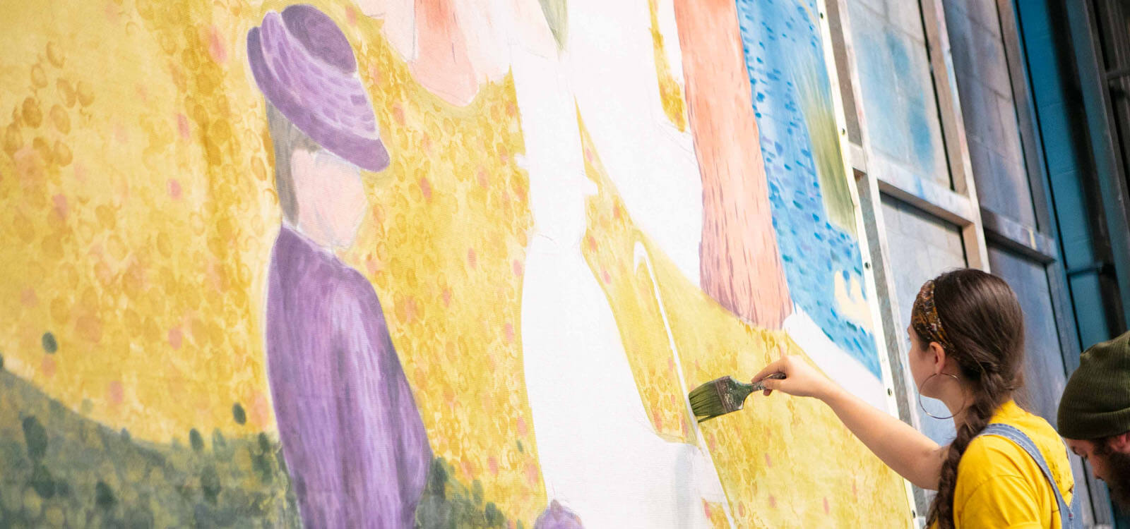 Production student painting a backdrop for Sunday in the Park with George