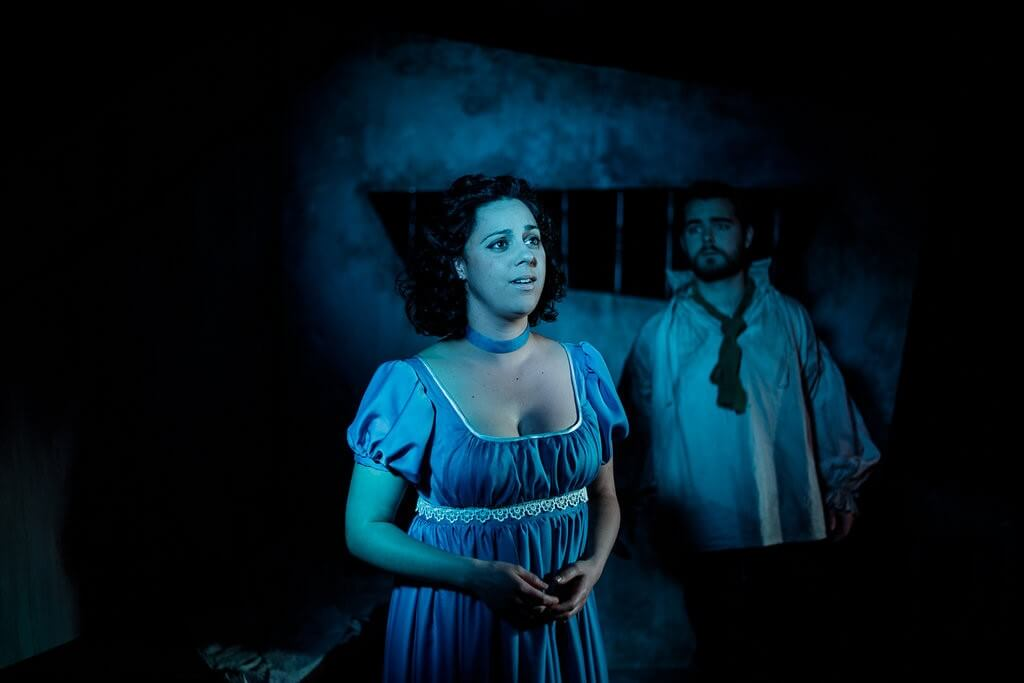 Woman wearing a blue dress looking off into the distance with a man standing in the background