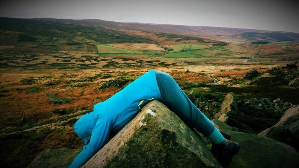 Sarah Hopfinger laying on a rock in the countryside