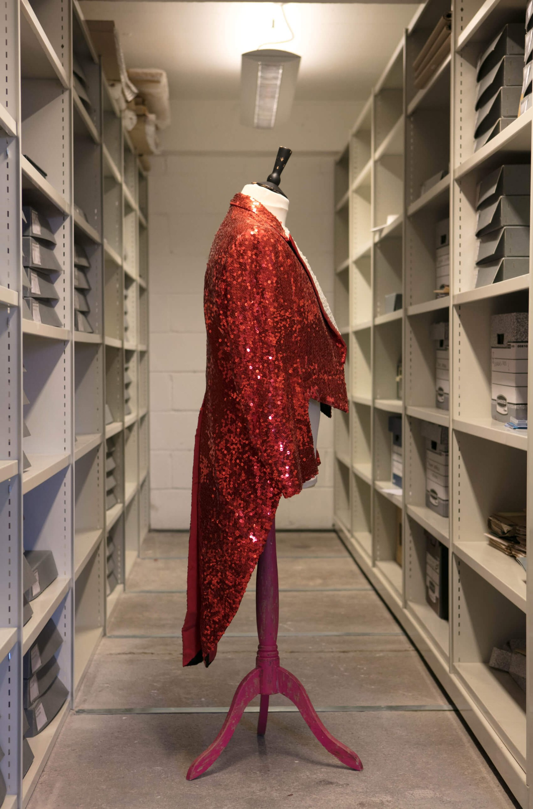 A red sequin tailcoat that was worn on stage by Scottish entertainer Jimmy Logan. It's displayed on a mannequin in the RCS archive