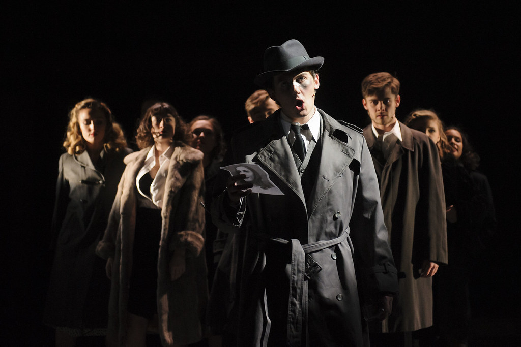 Cast of City of Angels wearing trenchcoats and looking to camera whilst singing