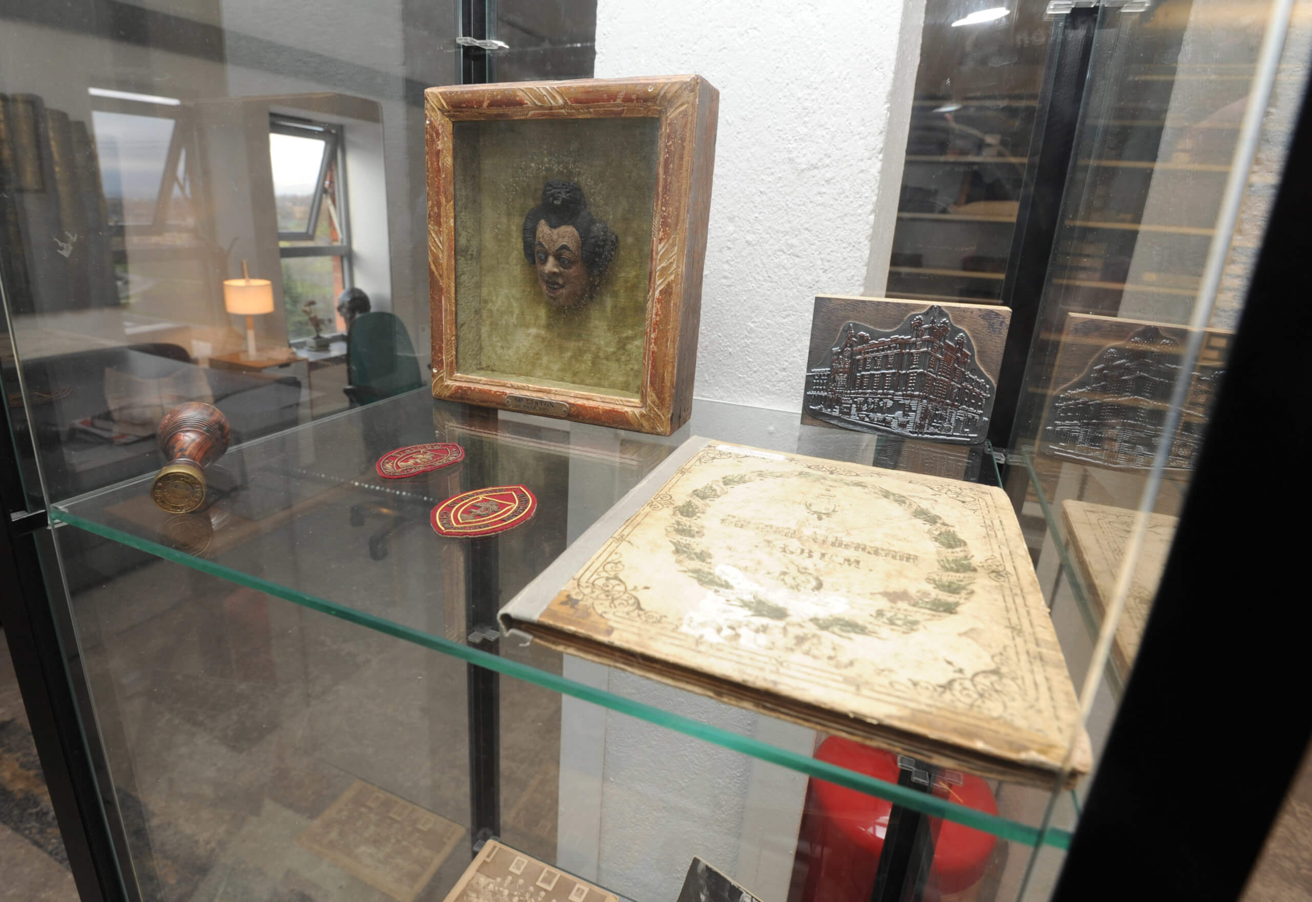 A glass display cabinet in the RCS archive is home to small trinkets and ornamental items