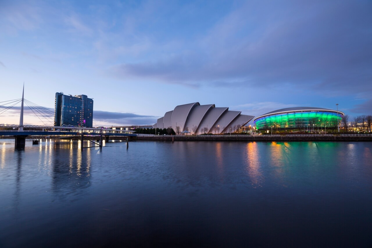 """A view of the Clyde Auditorium """"The Armadillo"""" (middle) & the SSE Hydro arena (right). Bells bridge is visible to the left with the Crowne Plaza Hotel illuminated behind. These attractions are located on the site of The Scottish Exhibition and Conference Centre, Glasgow."""