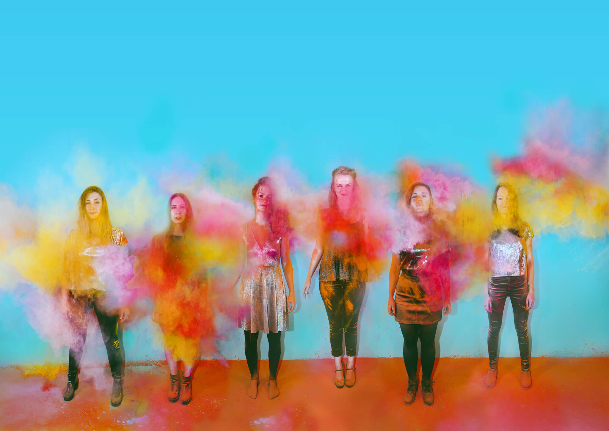 Six women stand in a line against a blue and orange backdrop. They are covered in paint powder which is also lingering in the air.