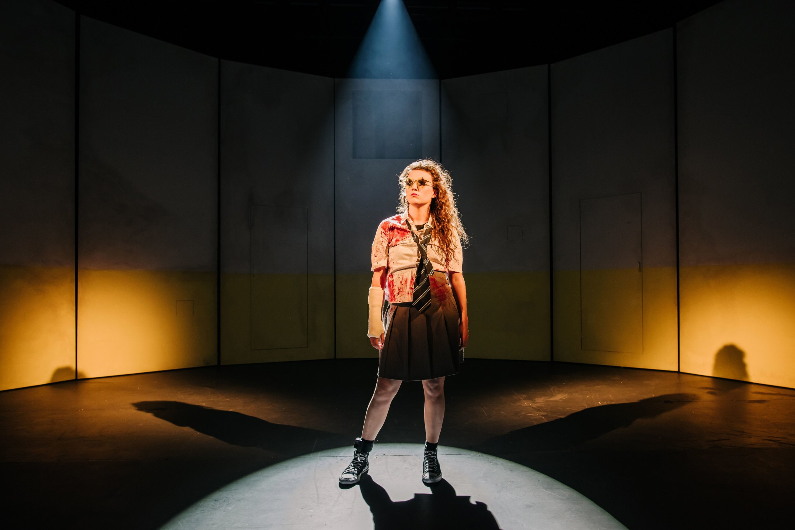 Anna Russell-Martin wears sunglasses as she stands on stage in the National Theatre of Scotland's production of the play The Panopticon.