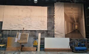 Behind the scenes of painting a backdrop image for a performance of City of Angels. The work in progress is positioned to the left of the backcloth from the MGM film of the same name.