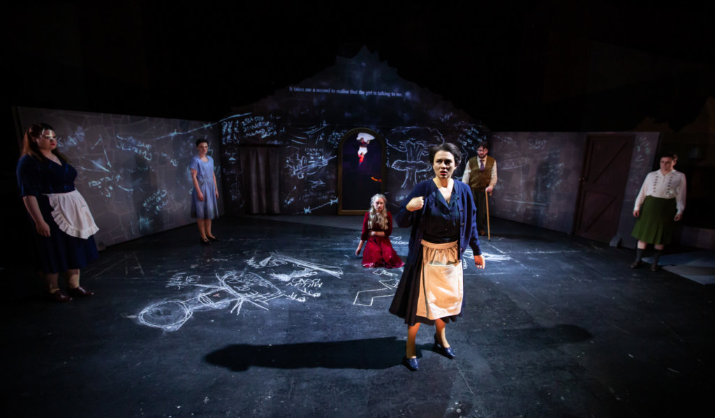 Six performers stand in a room with chalk drawings on the walls & floor