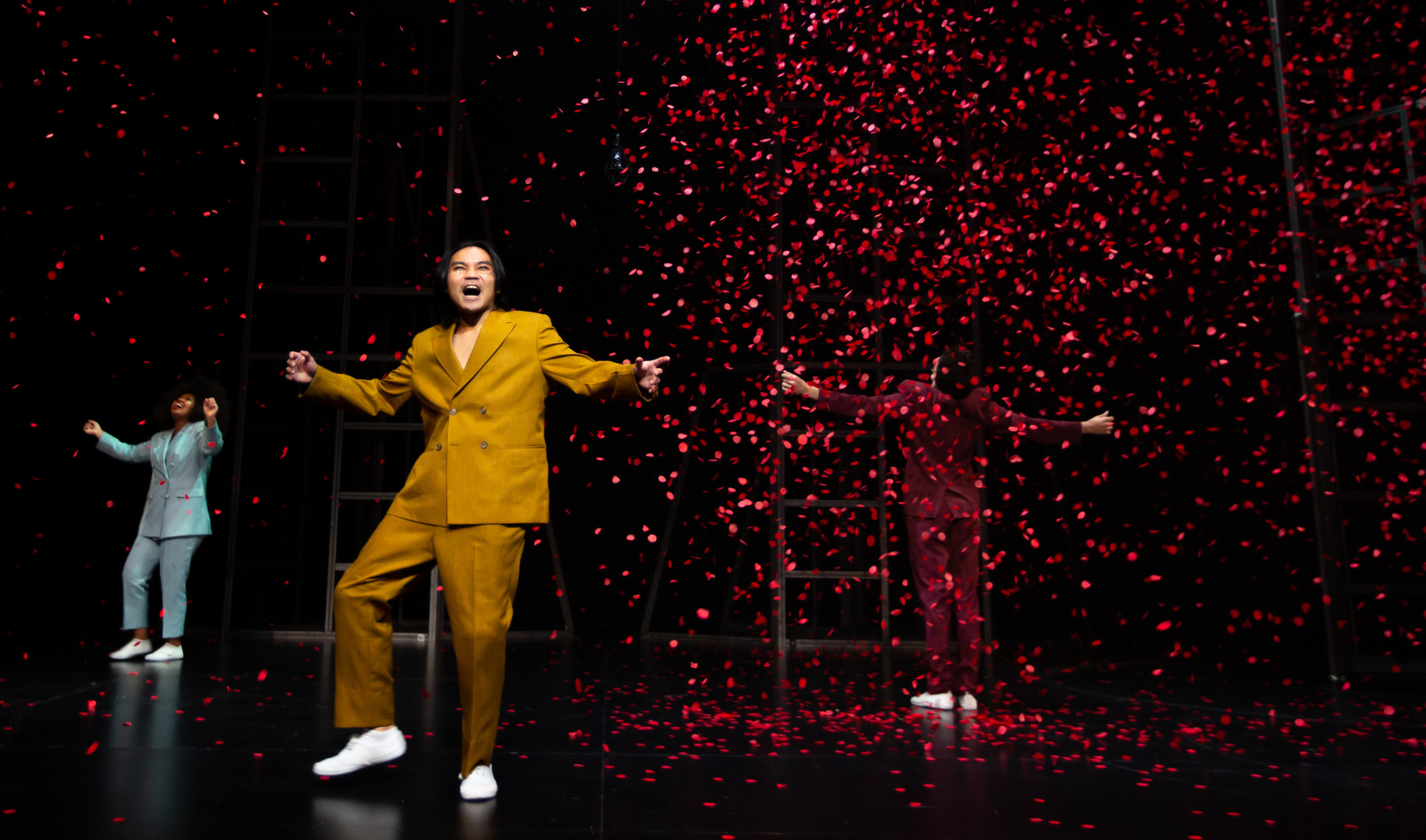 Student wearing yellow suit standing on a dark stage with red confetti falling behind them