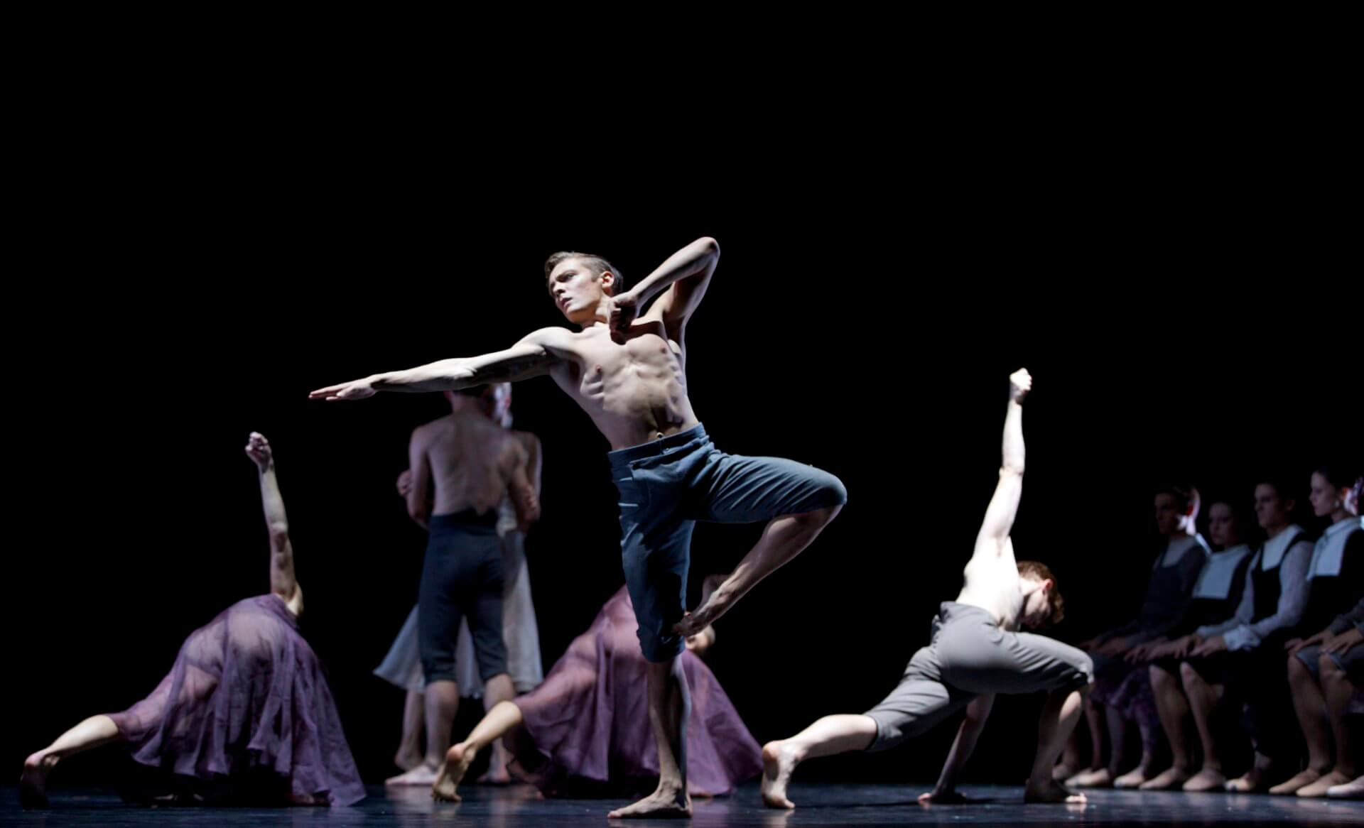 Jamiel Laurence dancing in the middle of the stage with dancers behind him