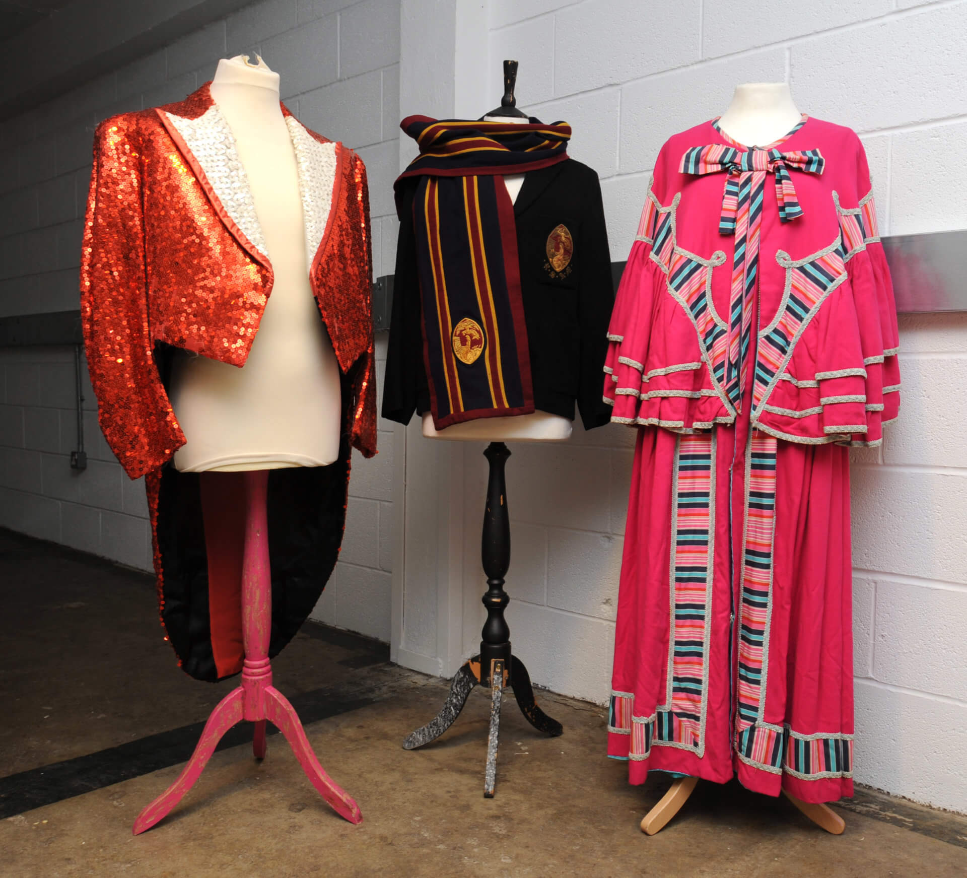 Costumes worn by Scottish entertainer Jimmy Logan are displayed on  mannequins in the RCS archive - a red sequin tailcoat and a pink pantomime dame dress. In the middle is a blazer worn by RCS music students in the 1950s.