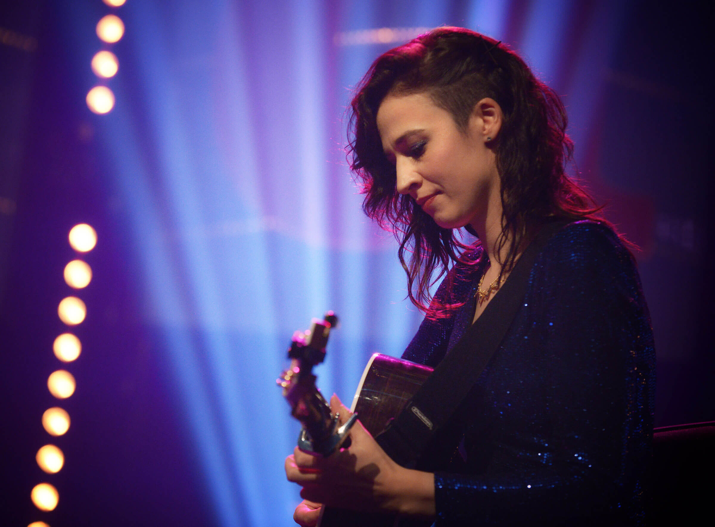 Folk guitarist Jenn Butterworth plays the guitar on stage in front of a purple stage light