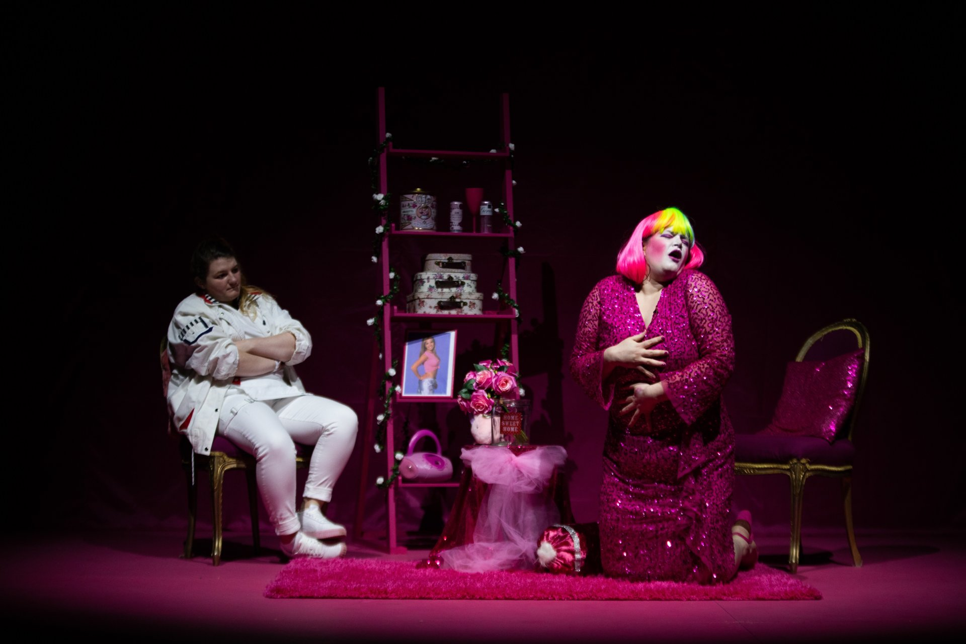 Two performers sit on stage surrounded by pink props. The performer on the right wears a pink sequin dress and pink wig while the performer to the left wears a white patterned jacket and trousers and sits with their arms folded. It's part of Into the New, the festival of contemporary performance at RCS