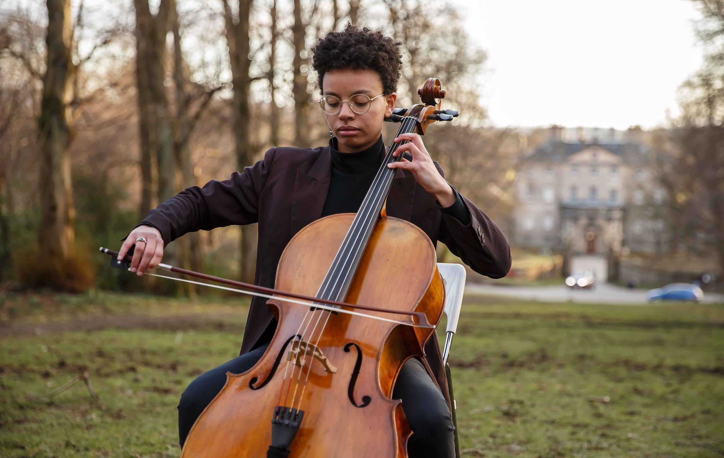 Student Simone Seales sits on a chair in Pollok Park and plays the cello