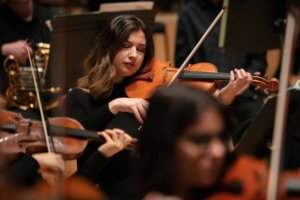 A violinist plays in a symphony orchestra with eyes closed