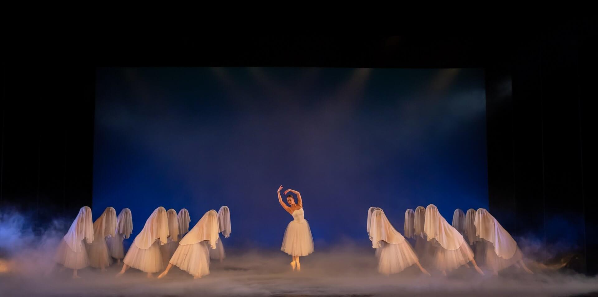 A scene from the ballet Giselle with a ballerina in long white tutu at centre stage with dancers in lines at either side, all wearing white tutus and veils draped over their heads