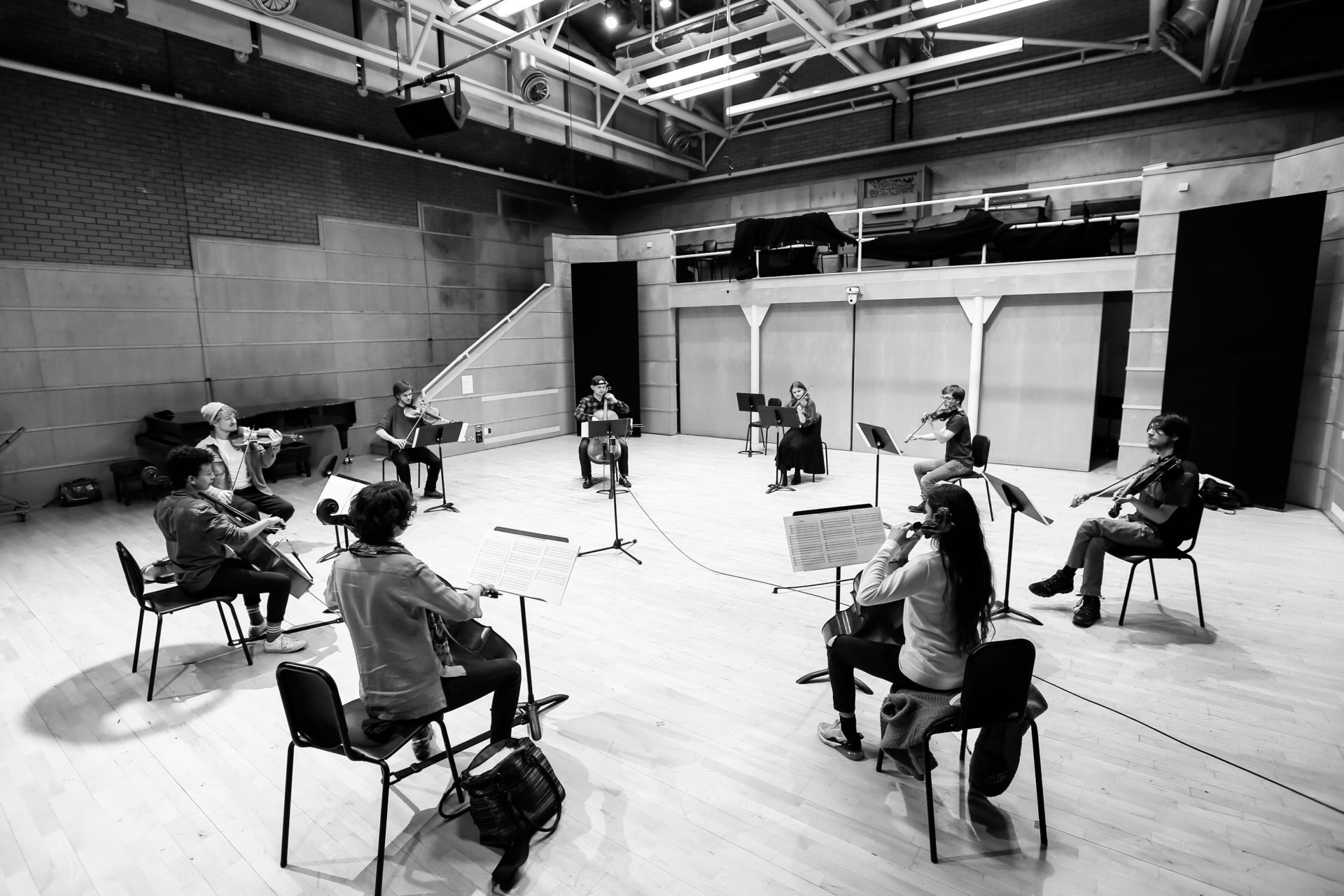 B&W image of string musicians called Studio Collective sitting in a circle in a concert hall at the Royal Conservatoire of Scotland with violinist and RCS associate artist Daniel Pioro.