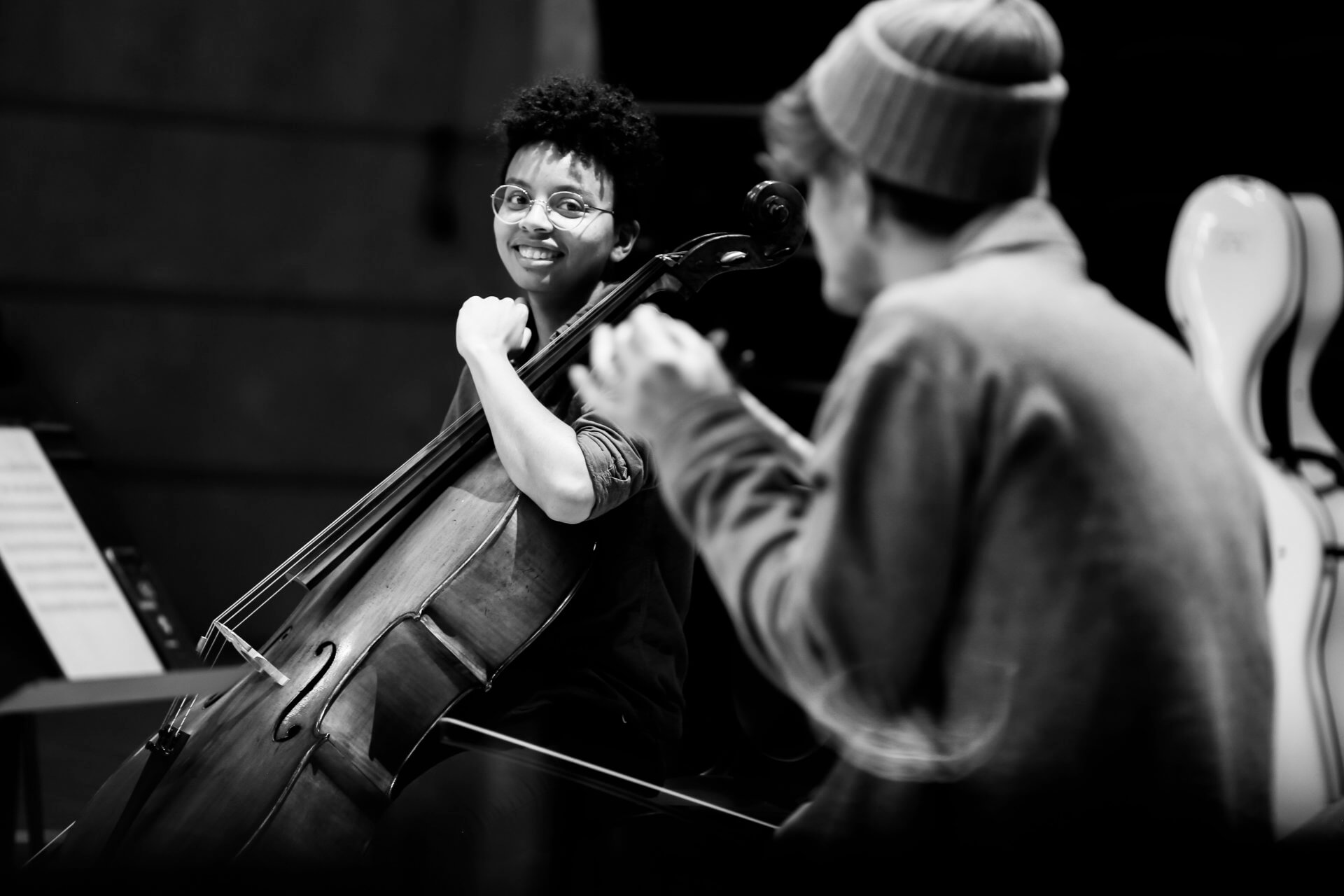 B&W image of RCS student Simone Seales smiling and looking at Daniel Pioro, who has his back to the camera. Simone is part of Studio Collective. She is pictured holding her cello.