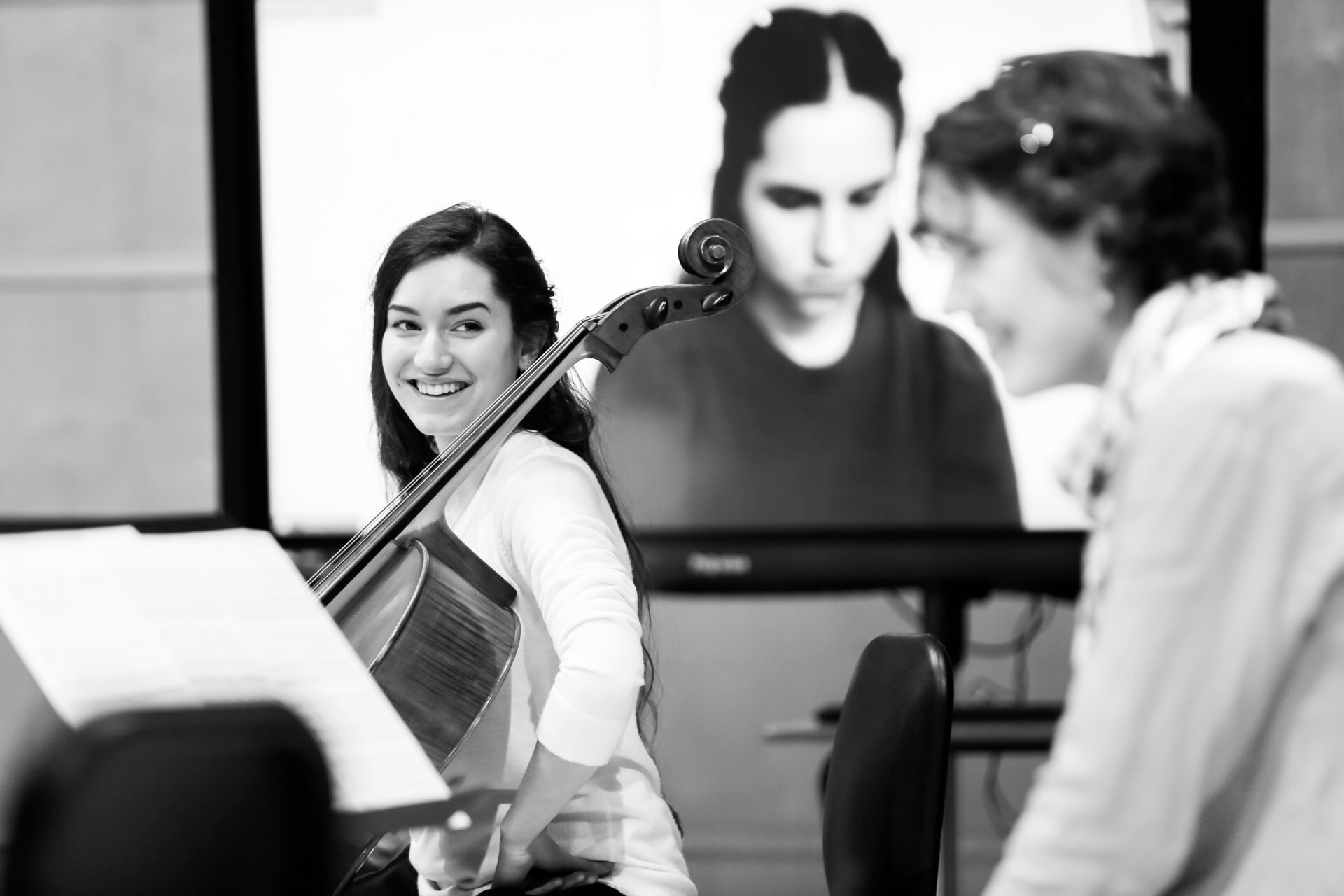 B&W image of RCS student, cellist Rebekah Lesan who is smiling and looking off to her Studio Collective colleague Madelyn Kowalski, who is also a cellist