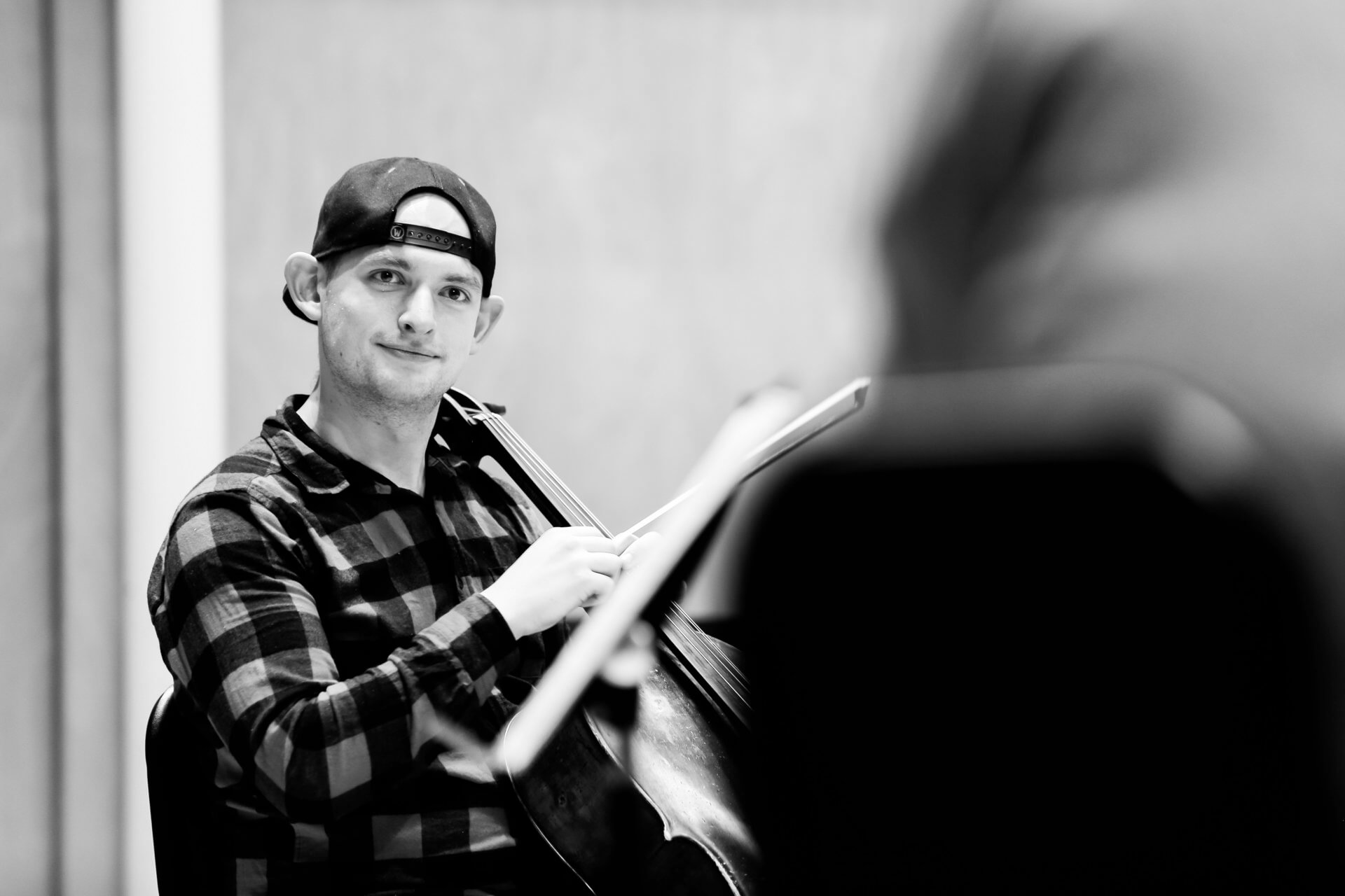 B&W image of cellist and RCS student Cameron Smith engaging with a fellow Studio Collective musician