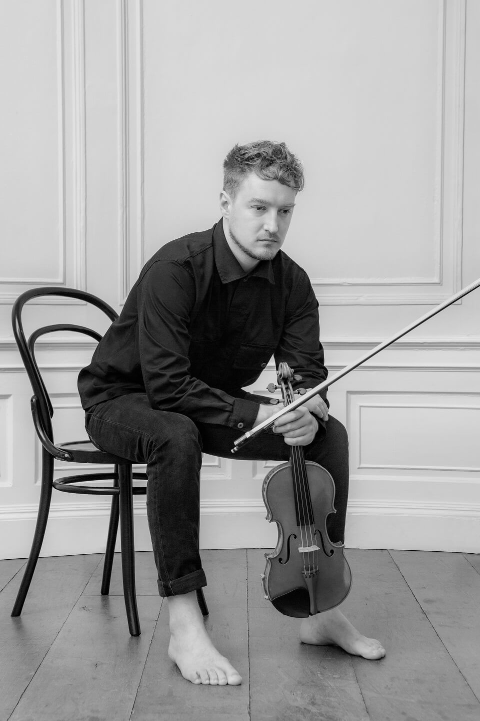 B&W image of Daniel Pioro wearing a black shirt and trousers sitting on a bistro chair, with violin and bow in his hands