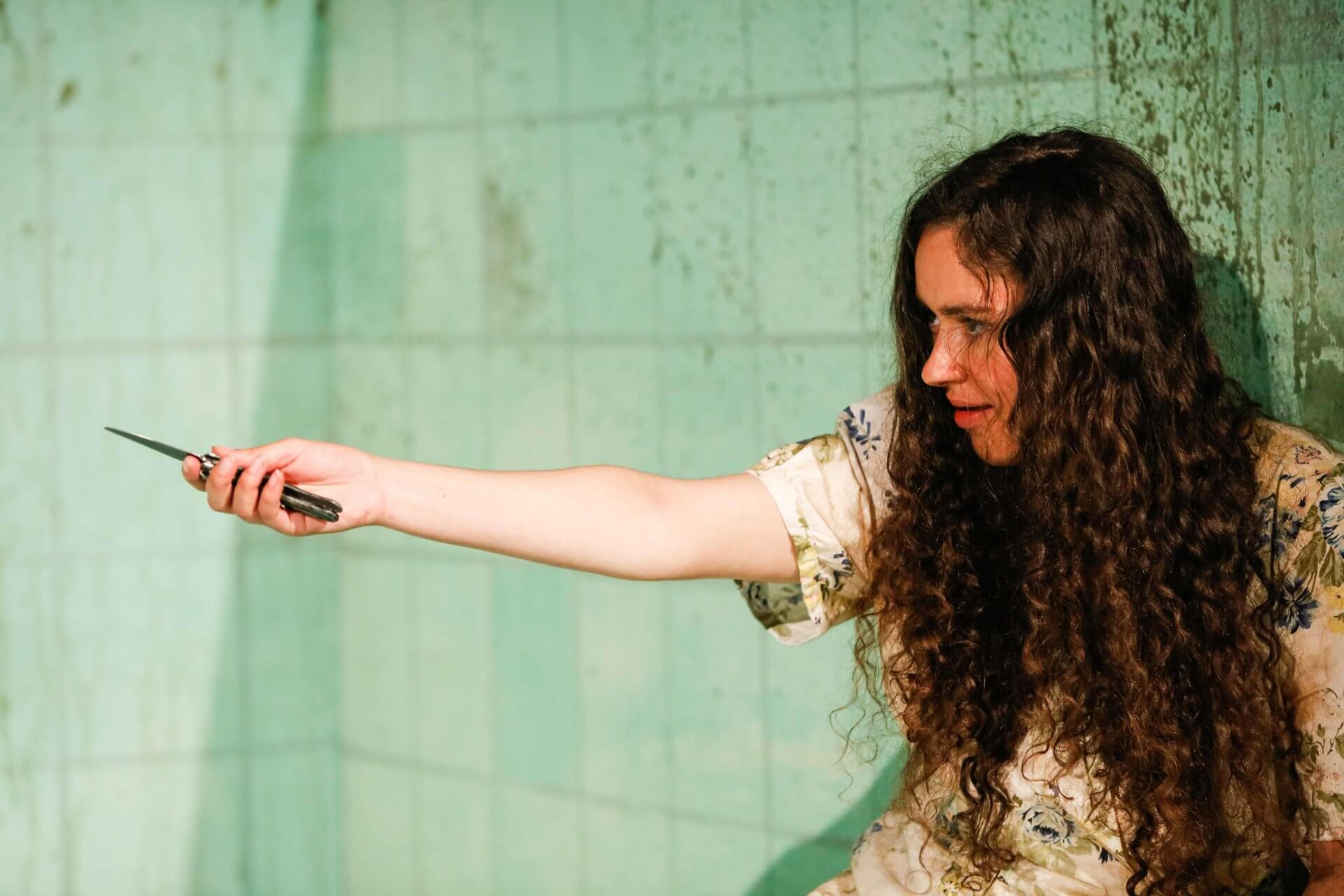 Unmissable new theatre at RCS. A performer with long brown hair stands against a tiled wall with a knife outstretched in their hand