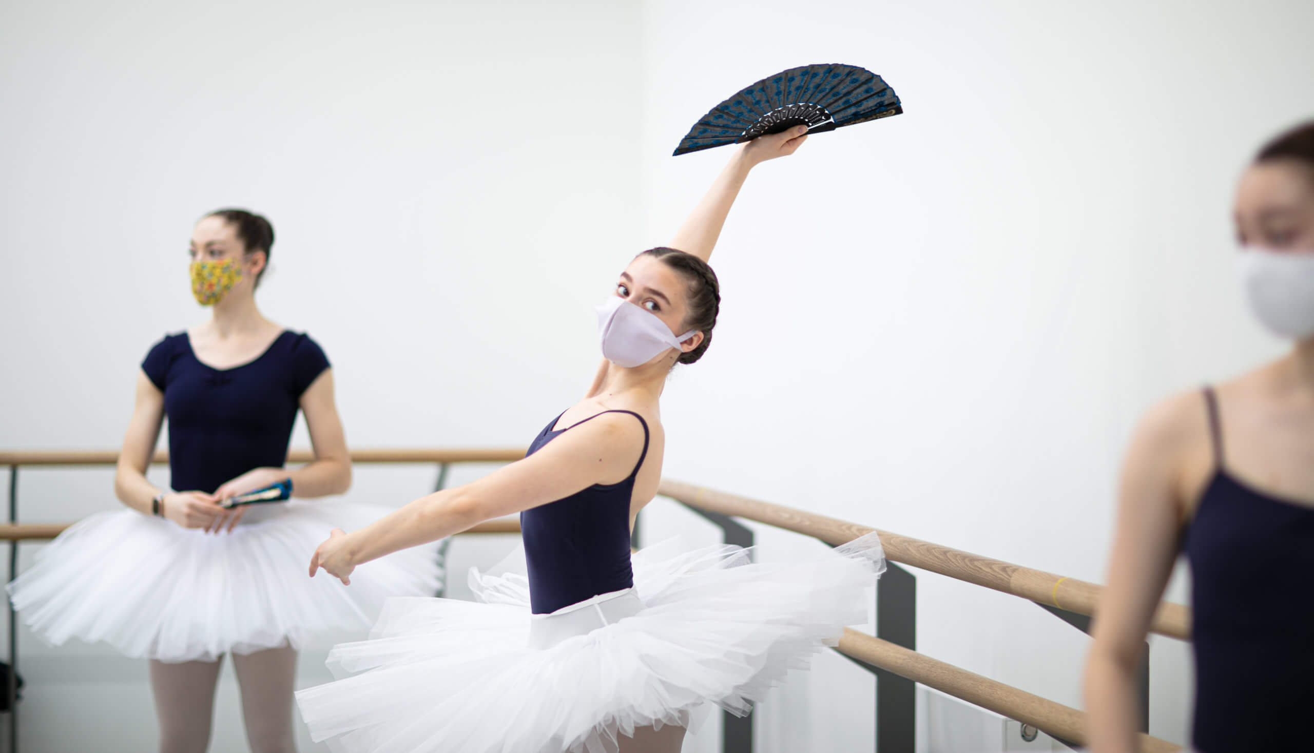 Three ballet dancers in the studio at Speirs Locks. The dancer in the centre is holding a fan aloft