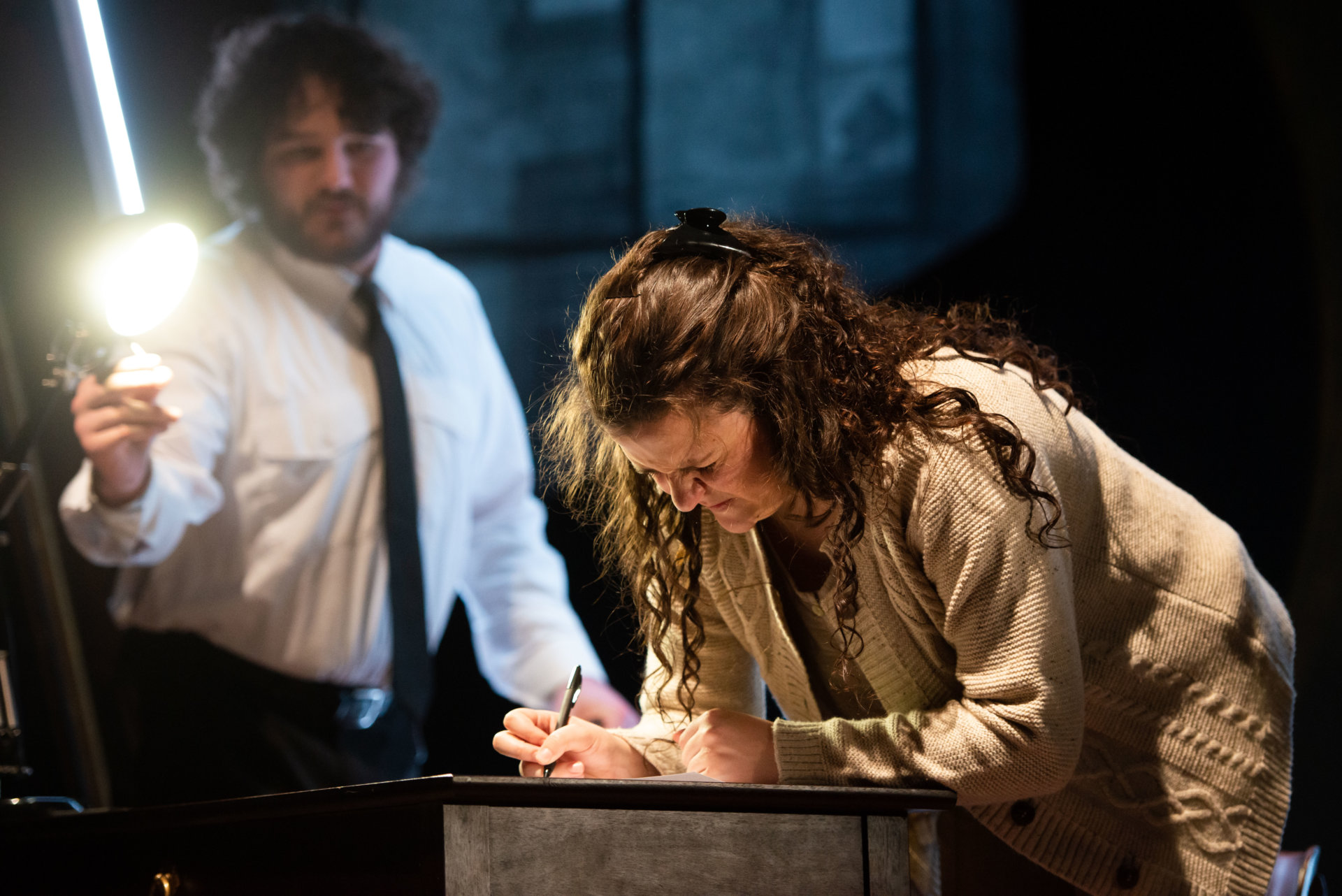 A person leans over a table writing while another points a light in their direction
