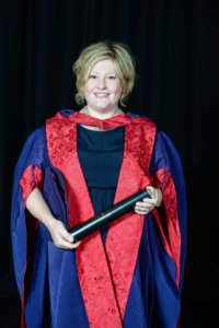 Karen Cargill is wearing her honorary doctorate degree robes and carrying a scroll as she smiles into the camera.